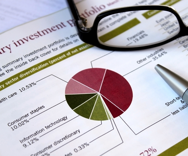financial concept - pie chart showing investment portfolio breakdown, glasses and pen support analysis,review theme